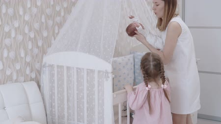 lánya : Young mother holding her cute newborn baby boy. Slow motion family concept video.