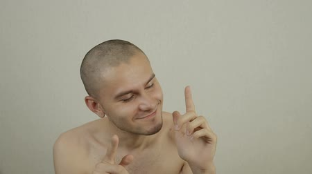 молодой взрослый человек : Portrait of a young bald man dancing before the camera.