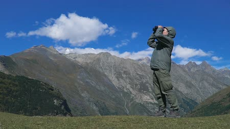 binocular : Man looking through binoculars at the mountains Stock Footage