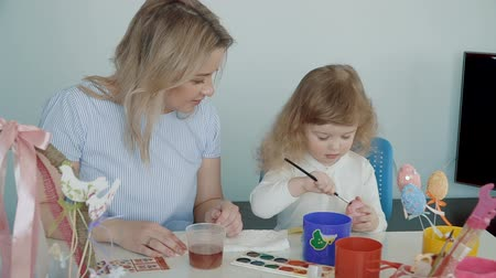 Mother and her little daughter painting Easter eggs at the festive table with basket and eggs. Slow Motion