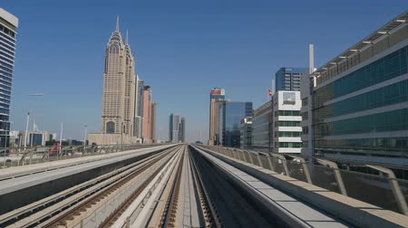 metro : DUBAI, UAE - DECEMBER 12, 2018: Modern Dubai Metro train travels on rails along the high-rise buildings in Dubai, UAE.