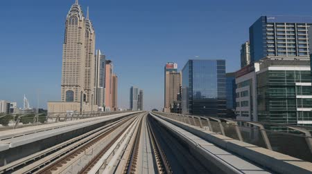 tramwaj : DUBAI, UAE - DECEMBER 12, 2018: Modern Dubai Metro train travels on rails along the high-rise buildings in Dubai, UAE.