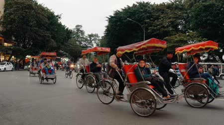 rickshaw : HANOI, VIETNAM - DECEMBER 14, 2018: Tourists ride a rickshaws in the old center of Hanoi - capital of Vietnam.