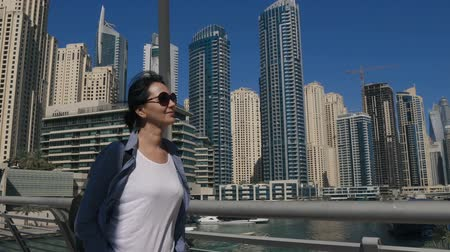 A happy woman walking street in Dubai on a background of skyscrapers at Dubai Marina. Wideo