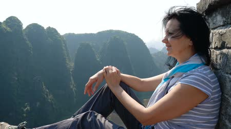 Attractive woman sitting on the edge of the cliff against high rocky mountains, admiring beautiful views of from above at Tam Coc, Ninh Binh Province, Vietnam.