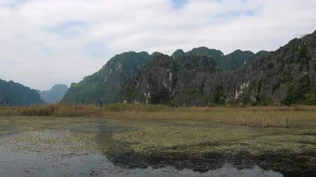 Panorama view of beautiful karst scenery, wetlands seen from the boat at Van Long Nature Reserve, Vietnam. Tourists traveling in small boat in tranquil landscape.