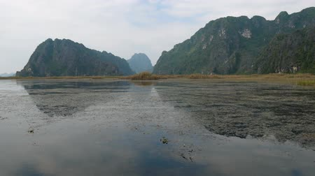 kürek çekme : Panorama view of beautiful karst scenery, wetlands seen from the boat at Van Long Nature Reserve, Vietnam. Tourists traveling in small boat in tranquil landscape.