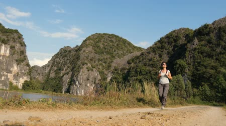 インドシナ : Hiking outdoors on nature - pretty woman walking through beautiful wetlands in Vietnam. Walking the trek with backpack.