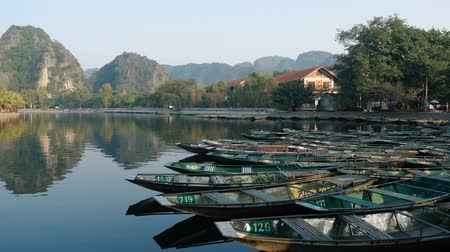 ninh : TAM COC, VIETNAM - DECEMBER 17, 2018: Tam Coc boat station. Popular boat tour - tourists traveling in small boat admiring beautifull landscape formed by limestone mountains and rice fields.