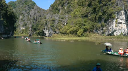 kalker : TAM COC, VIETNAM - DECEMBER 17, 2018: Panorama view of beautiful karst scenery, river and rice paddy fields. Tourists traveling in small boat along the river, Ninh Binh Province, Vietnam