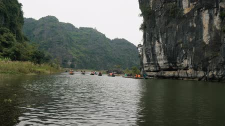 ninh : TAM COC, VIETNAM - DECEMBER 17, 2018: Panorama view of beautiful karst scenery, river and rice paddy fields. Tourists traveling in small boat along the river, Ninh Binh Province, Vietnam