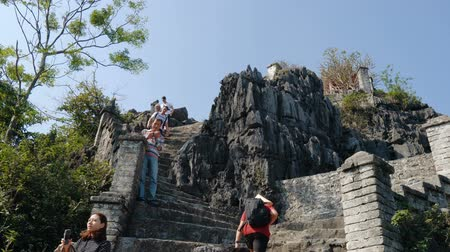 ninh : TAM COC, VIETNAM - DECEMBER 19, 2018: Popular vietnam destination - people climb the mountain, 500 steps to a lookout with iconic views of the countryside Stock Footage