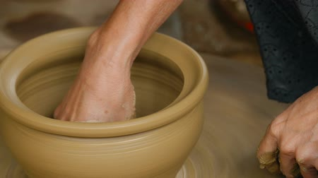 Close up of woman hands working clay on potters wheel. Potter shapes the clay pot with hands on the potters wheel, craft factory authentic.