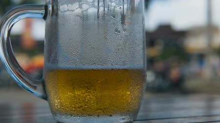 quartilho : Cold light beer in a glass with water drops. Craft beer on the table at the street restaurant.