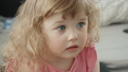 Portrait of a little cute girl watching tv. Slow motion family concept video.