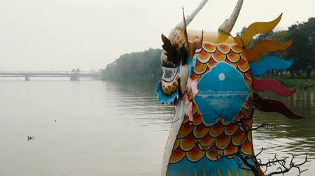 docked : Dragon boat moving up the Perfume River on a cloudy day, Hue, Vietnam