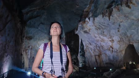 gat in muur : Pretty woman with photo camera walking and exploring through a giant Paradise Cave in Phong Nha Ke Bang National Park, Vietnam. Stockvideo