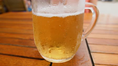 fabricado cerveja : Cold light beer in a glass with water drops. Craft beer on the table at the street restaurant.