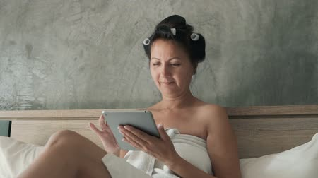 Attractive woman wearing hair rollers sitting on a double bed and drinking coffee after the shower in the morning.