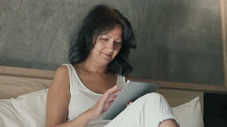 Attractive woman wearing a white t shirt sitting on a double bed, using her digital tablet and smiling. Wideo