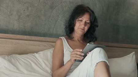 Attractive woman wearing a white t shirt sitting on a double bed, using her digital tablet and smiling. Dostupné videozáznamy