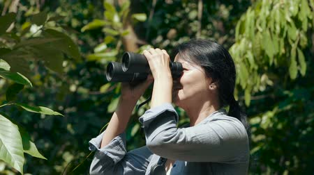 Woman looking through binoculars at the trees, enjoying the view at asian jungle. Trekking through the jungle.