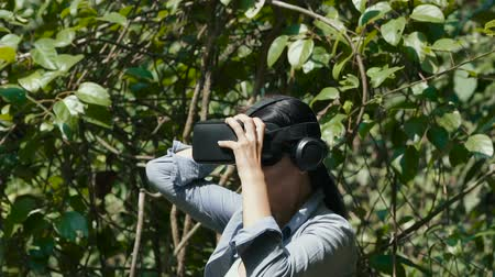 Woman with virtual reality goggles outdoors. Green jungle trees background on sunny day. Technology, virtual reality, entertainment and people concept