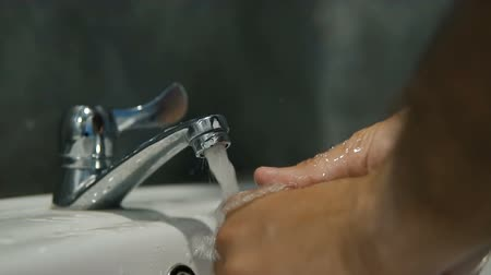 turning off : Slow motion - turning water on and washing hands, close up of bathroom sink.