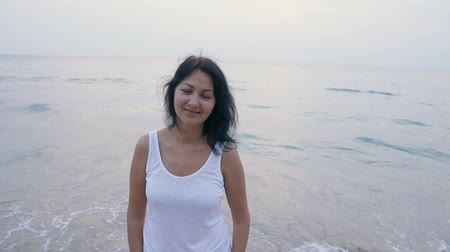 rendes : Portrait of attractive smiling woman on a tropical beach at sunset. Slow motion people footage. Stock mozgókép