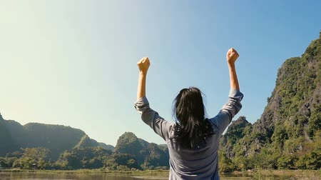 montanhas rochosas : Slow motion - attractive happy woman standing and raising her hands up against high rocky mountains, admiring beautiful views, Vietnam.