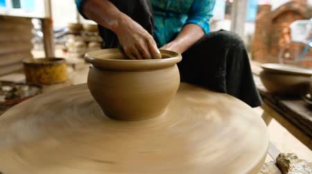 kamenina : Close up of woman hands working clay on potters wheel. Potter shapes the clay pot with hands on the potters wheel, craft factory authentic.