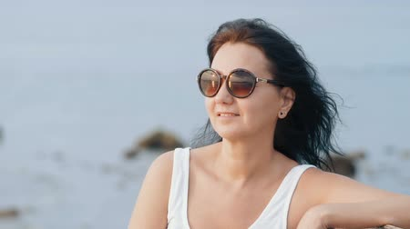 rendes : Portrait of attractive smiling woman watching sunset on a tropical beach. Slow motion people footage. Handheld camera. Stock mozgókép