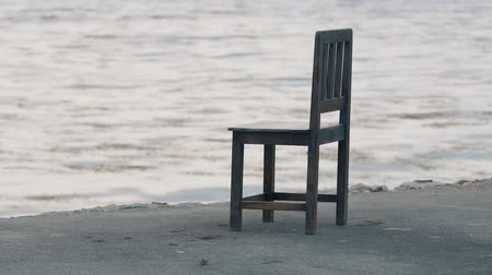 leegte : Single chair at the seafront. Sea waves moving slowly.