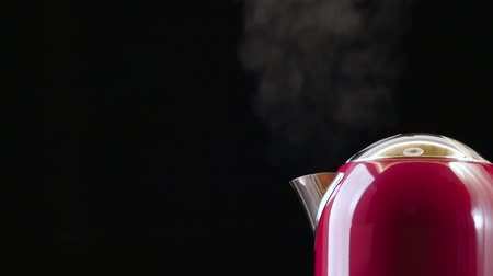 konvice : Boiling red kettle on the black background