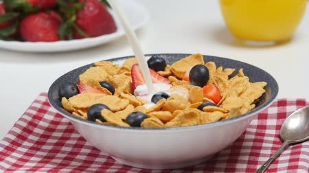 flocos de milho : Morning breakfast. Milk pouring into bowl with cornflakes and berries