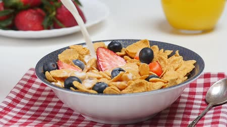 cereais : Morning breakfast. Milk pouring into bowl with cornflakes and berries