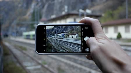 Tourist taking photo with smartphone on the railway station. Lombardia, Italy Stock mozgókép