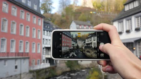 Tourist taking a photo of the beautiful river. Monschau, Germany Stock mozgókép
