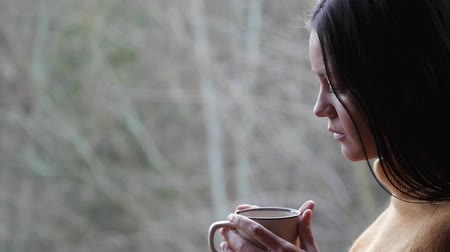 Sad woman with cup of coffee on the forest background Stock mozgókép