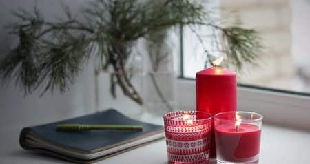 Candles and notebook on a windowsill