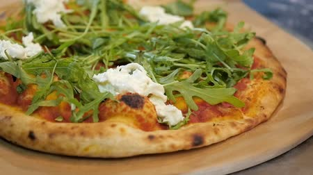 Chef puts stracciatella cheese on pizza