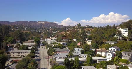 fama : Hollywood sign district in Los Angeles, USA. Beautiful Hollywood highway road with cars, palms and a sign on the hills. Clear blue sky. Stock Footage