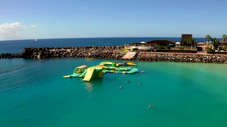 kanári : July 10. 2018 - Amadores beach, Gran Canaria, Spain: Small children and kids playing on the water playground city at the Amadores beach