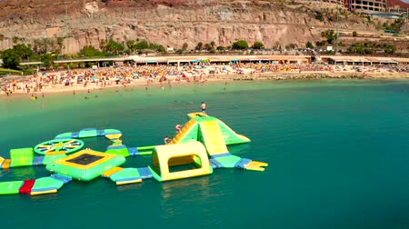 July 10. 2018 - Amadores beach, Gran Canaria, Spain: Small children and kids playing on the water playground city at the Amadores beach