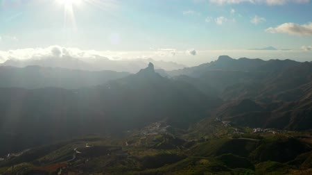 Aerial mountain view of the Gran Canaria island with Tenerife Teide Volcano visible above the clouds.