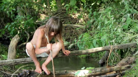 pesquisa : boy playing near forest stream