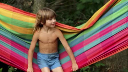 menino : boy swinging on a hammock