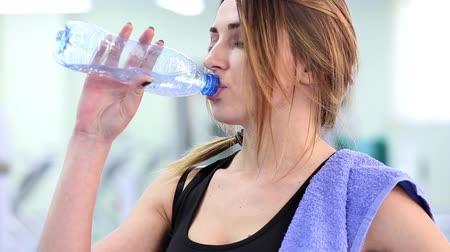 sportovní : Gym work out young women,Young  beauty woman exercising at a gym(drinking water) Dostupné videozáznamy