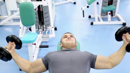 kaslı : man at the gym, training of the pectoral muscles with dumbbells