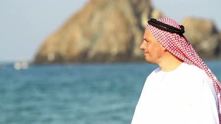 головной убор : Arabian man,on the beach.Arab man walks along the sea